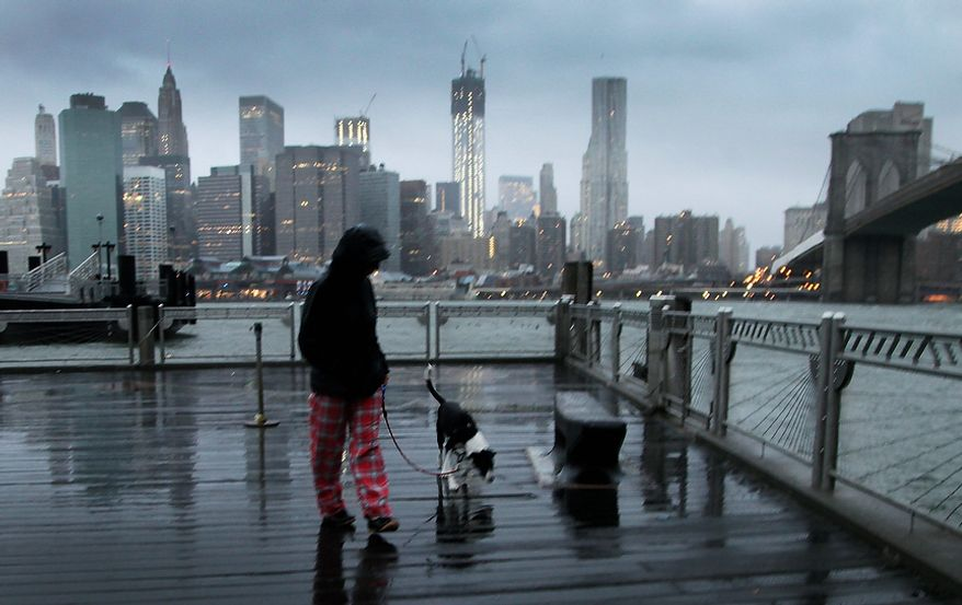 Vanessa Pumo walks her dog, Bella, as wind and rain from Hurricane Sandy arrive on Monday, Oct. 29, 2012, in the Brooklyn borough of New York. Behind her is the Manhattan skyline and the Brooklyn Bridge (right). (AP Photo/Mark Lennihan)