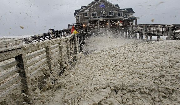 High winds blow sea foam onto Jeanette's Pier in Nags Head, N.C., on Sunday, Oct. 28, 2012, as wind and rain from Hurricane Sandy move into the area. Governors from North Carolina, where steady rains were whipped by gusting winds Saturday night, to Connecticut declared states of emergency. Delaware ordered mandatory evacuations for coastal communities by 8 p.m. Sunday. (AP Photo/Gerry Broome)