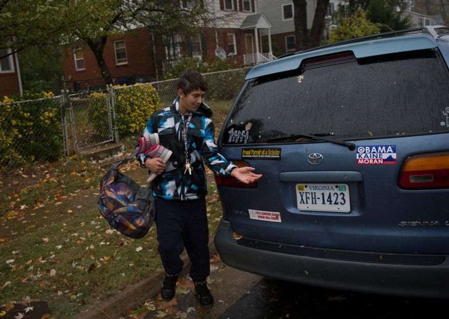 A young man removes belongings from a home on Arlington Terrace in the Huntington neighborhood of Alexandria, Va., on Oct. 29, 2012, during a mandatory evacuation order as high winds and heavy rain from Hurricane Sandy pound the Atlantic coast. (Rod Lamkey Jr./The Washington Times)