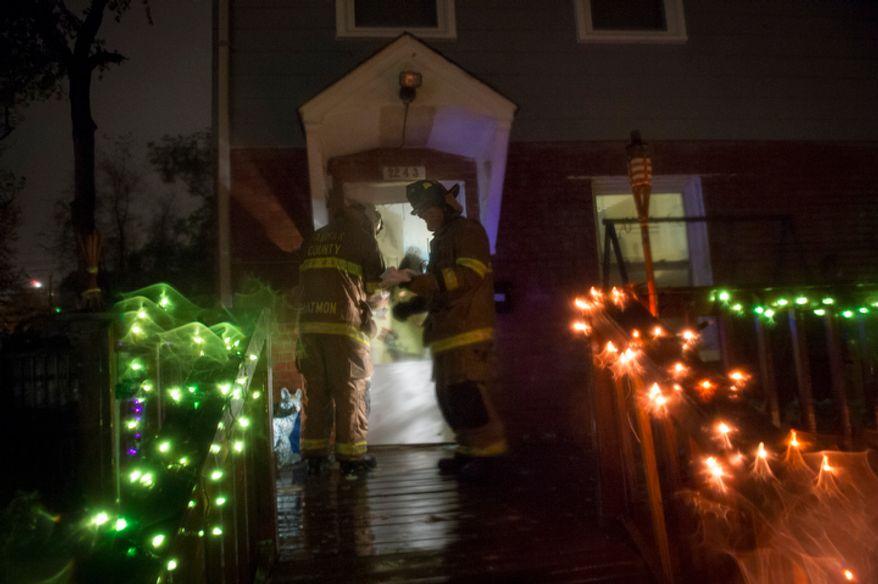 Fairfax County firefighters go door to door to check on residents on Arlington Terrace in the Huntington neighborhood of Alexandria, Va., on Oct. 29, 2012, during a mandatory evacuation order as high winds and heavy rain from Hurricane Sandy pound the Atlantic coast. (Rod Lamkey Jr./The Washington Times)