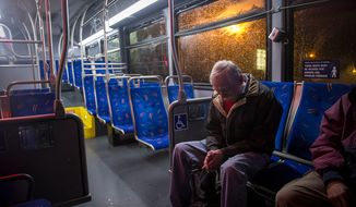 Michael Murphy waits on a city bus to be taken to a shelter at the Lee District RECenter in Franconia, Va., during a mandatory evacuation order in the Huntington neighborhood of Alexandria, Va., on Oct. 29, 2012, as high winds and heavy rain from Hurricane Sandy pound the Atlantic coast. Mr. Murphy's home is on Arlington Terrace in Huntington. (Rod Lamkey Jr./The Washington Times)