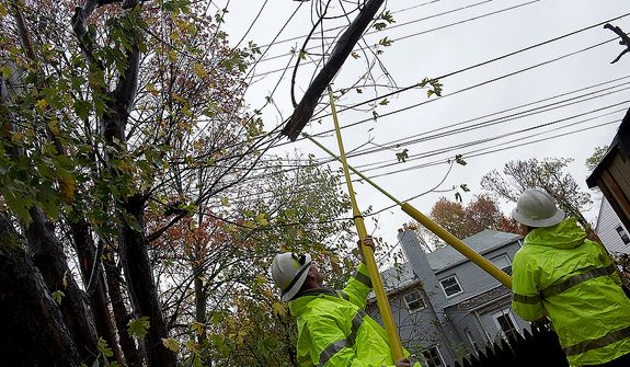 Dominion Power workers Brandon Zaluksi [cq], left, and Brian Moore use extend-o sticks to remove a tree branch from a communications wire in the backyard of a Huntington, Va. resident on Monday, Oct. 29, 2012. They said that calls to Dominion Power are already coming at a steady rate, hours before Hurricane Sandy is expected to make landfall. (Barbara L. Salisbury/The Washington Times)