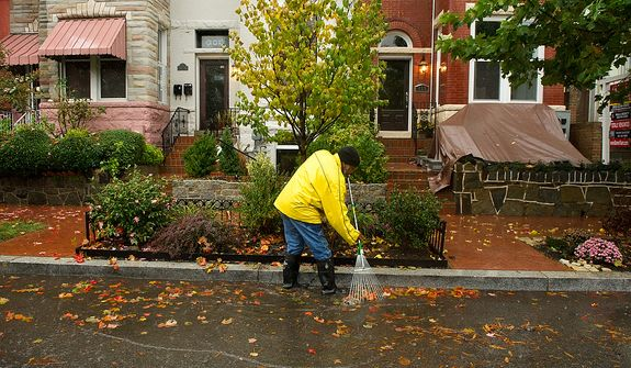 David Brooks clears leaves from a gutter along a section of Rhode Island Avenue that has been prone to flooding from big storms in the Bloomingdale neighborhood of Northwest, Washington, D.C., Monday, October 29, 2012. Hurricane Sandy begins to affect the Washington, D.C. region. (Andrew Harnik/The Washington Times)