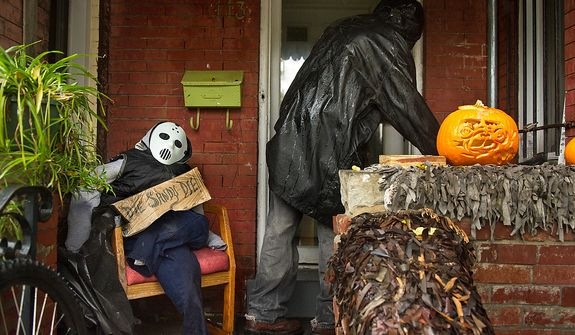 "Clyde Forbes walks into the front of his house past a halloween pumkin and maniquen with a sign that reads ""Die Sandy Die!"" along a section of Rhode Island Avenue that has been prone to flooding from big storms in the Bloomingdale neighborhood of Northwest, Washington, D.C., Monday, October 29, 2012. Hurricane Sandy begins to affect the Washington, D.C. region. (Andrew Harnik/The Washington Times)"