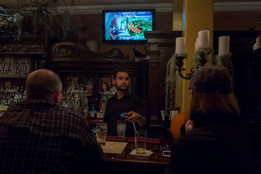 O'Connell's Restaurant server Mike Doran, of Waldorf, Md., takes care of customers as they watch the progress of Hurricane Sandy on the television in Old Town Alexandria, Va., Monday, Oct. 29, 2012, while Hurricane Sandy makes it's way north along the Atlantic coast. (Rod Lamkey Jr./The Washington Times)