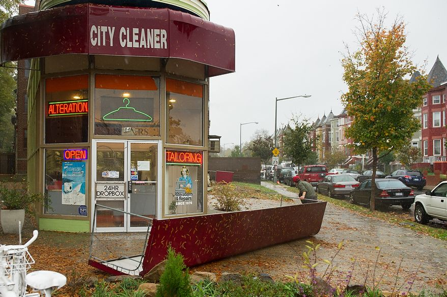 Se Kim [cq] with City Cleaners drags awnings that were removed for a renovation project to the back of the store away from the wind along Rhode Island Avenue in the Bloomingdale neighborhood of Northwest, Washington, D.C., Monday, October 29, 2012. Hurricane Sandy begins to affect the Washington, D.C. region. (Andrew Harnik/The Washington Times)