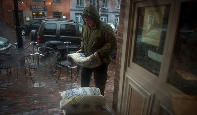 O'Connell's Restaurant General Manager Doug Gruenberg carries sand bags to put into place at the restaurant's doorsteps in Old Town Alexandria, Va., Monday, Oct. 29, 2012, while Hurricane Sandy makes it's way north along the Atlantic coast. (Rod Lamkey Jr./The Washington Times)