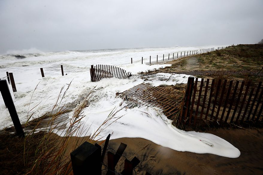Sea foam washes over the beach as Hurricane Sandy bears down on the East Coast, Monday, Oct. 29, 2012, in Ocean City, Md. Hurricane Sandy continued on its path Monday, as the storm forced the shutdown of mass transit, schools and financial markets, sending coastal residents fleeing, and threatening a dangerous mix of high winds and soaking rain. (AP Photo/Alex Brandon)