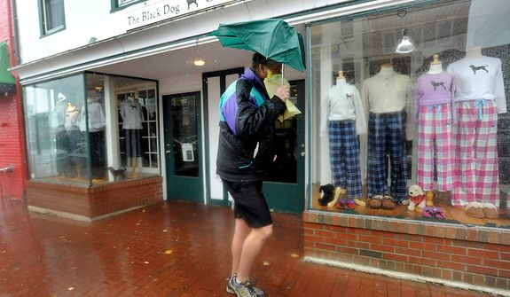 Anthony Reiner, of Annapolis, Md., tries to protect himself from rain and wind from Hurricane Sandy, Monday, Oct. 29, 2012, in Annapolis. Hurricane Sandy continued on its path Monday, as the storm forced the shutdown of mass transit, schools and financial markets, sending coastal residents fleeing, and threatening a dangerous mix of high winds and soaking rain. (AP Photo/Steve Ruark)