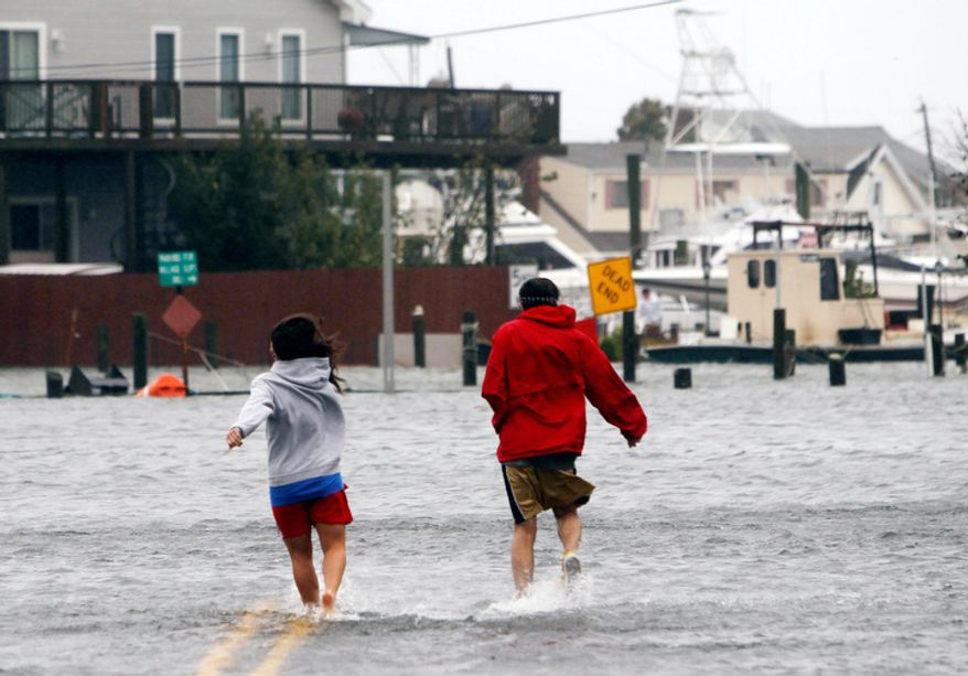 People run through a flooded street as Hurricane Sandy approaches, Monday, Oct. 29, 2012, in Lindenhurst, N.Y. Hurricane Sandy continued on its path Monday, as the storm forced the shutdown of mass transit, schools and financial markets, sending coastal residents fleeing, and threatening a dangerous mix of high winds and soaking rain. (AP Photo/Jason DeCrow)