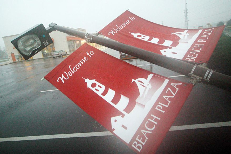 A parking light lies collapsed on the ground from strong winds in Rehoboth Beach, Del., Monday, Oct. 29, 2012. (AP Photo/The Wilmington News-Journal, Suchat Pederson)