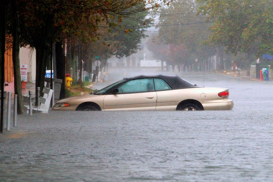 A car is stuck in deep water on Wilmington Avenue in Rehoboth Beach, Del., Monday, Oct. 29, 2012. (AP Photo/The Wilmington News-Journal, Suchat Pederson)