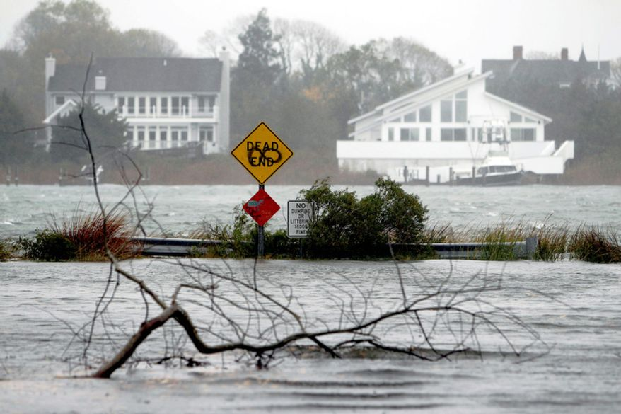 A downed limb lies in a flooded street as Hurricane Sandy approaches, Monday, Oct. 29, 2012, in Center Moriches, N.Y.  (AP Photo/Jason DeCrow)