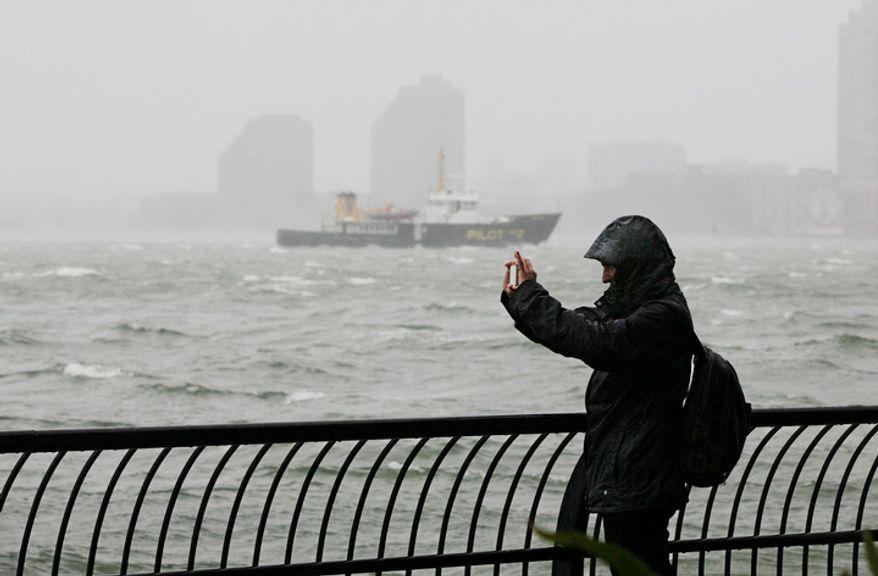 A woman uses her mobile phone to photograph New York Harbor at Battery Park, at the southern tip of Manhattan, Monday, Oct. 29, 2012. Defiant New Yorkers jogged, pushed strollers and took snapshots of churning New York Harbor on Monday, trying to salvage normal routines in a city with no trains, schools and an approaching mammoth storm. (AP Photo/Richard Drew)