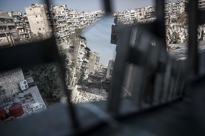 A street of shattered buildings is viewed partially through a mirror used by rebel fighters to keep an eye on their enemy's positions in the Karm al-Jabel battlefield in Aleppo, Syria, on Sunday, Oct. 28, 2012. Syria's air force fired missiles and dropped barrel bombs on rebel strongholds while opposition fighters attacked regime positions, flouting a U.N.-backed cease-fire that was supposed to quiet fighting over a long holiday weekend but never took hold. (AP Photo/Narciso Contreras)