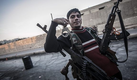 A rebel fighter poses for a photo holding handcuffs in the front-line neighborhood of Bustan Al-Pasha in Aleppo, Syria, shortly after an army jet hit the rebel position in the city's northwest. Syria's air force fired missiles and dropped barrel bombs on rebel strongholds while opposition fighters attacked regime positions, flouting a U.N.-backed cease-fire that was supposed to quiet fighting over a long holiday weekend but never took hold. (AP Photo/Narciso Contreras)