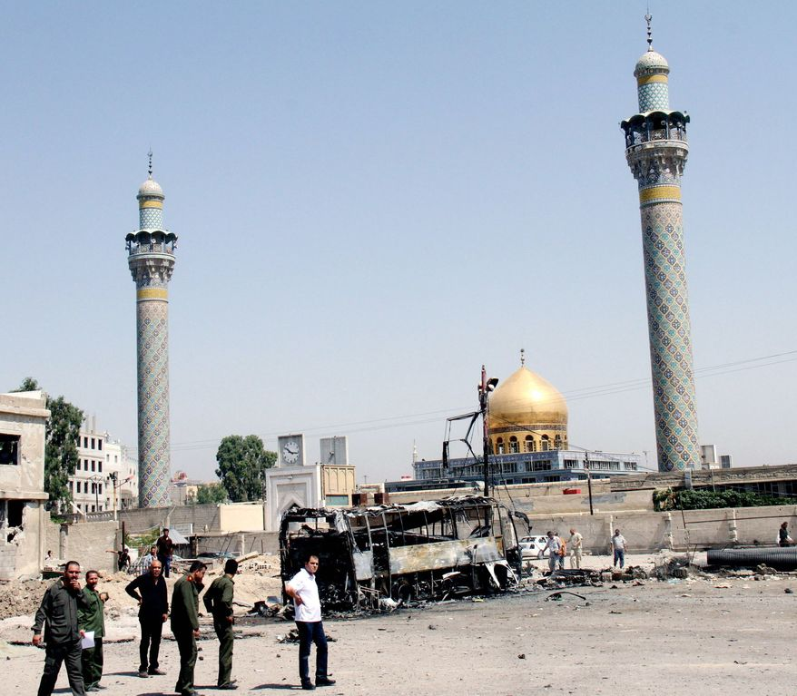 Syrian security forces are seen in June where a car bomb exploded near the Shiite shrine of Sayyida Zainab in a Damascus suburb. Iraqi Shiites fear targeting of their sect and holy sites if Bashar Assad falls. (Associated Press)
