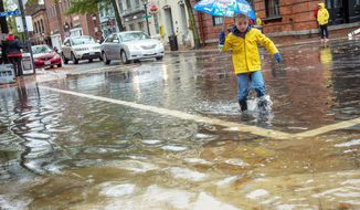 James McConnon, 5, of Alexandria, Va., crosses King Street by way of flood water, as people venture out to survey the damage in Old Town Alexandria, Va., Tuesday, Oct. 30, 2012, the day after Hurricane Sandy slammed into the region. Flood water here in Old Town is slightly higher than normal after a heavy rain. (Rod Lamkey Jr./The Washington Times)