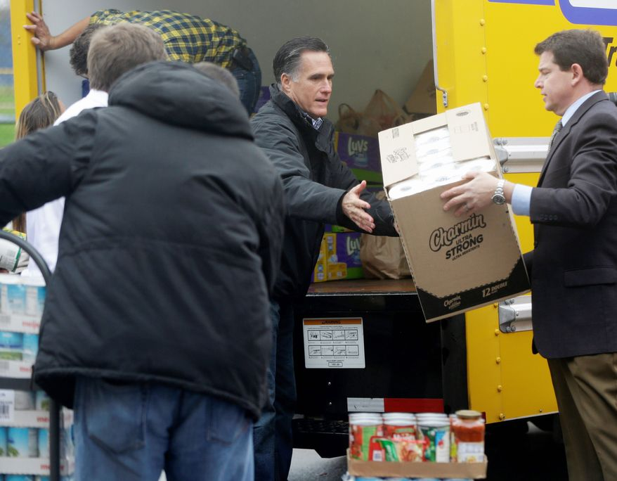 Republican presidential nominee Mitt Romney loads a truck with supplies Tuesday in Kettering, Ohio, during a rally to raise donations for those affected by Hurricane Sandy. Mr. Romney encouraged unity during the event while avoiding attacks on President Obama. (Associated Press)