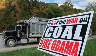 A truck passes a political sign in a yard in Dellslow, W.Va., on Oct. 16, 2012. (AP Photo/Vicki Smith) ** FILE **