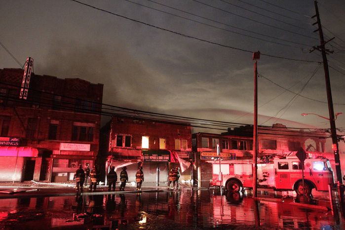 Firefighters battle a blaze on Rockaway Beach Boulevard in the borough of Queens on Tuesday, Oct. 30, 2012, in New York. (AP Photo/Frank Franklin II)