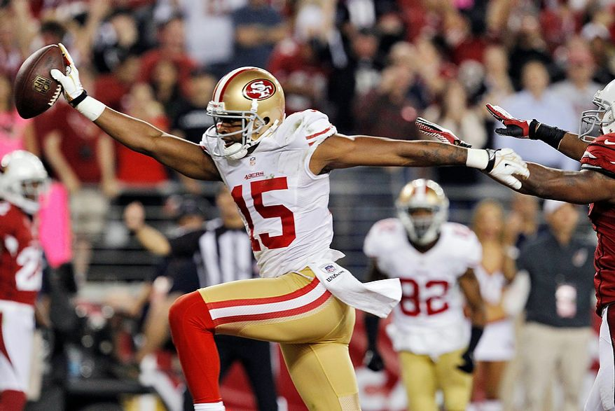 San Francisco 49ers wide receiver Michael Crabtree (15) scores a touchdown against the Arizona Cardinals during the first half of an NFL football game on Monday, Oct. 29, 2012, in Glendale, Ariz. (AP Photo/Ross D. Franklin)