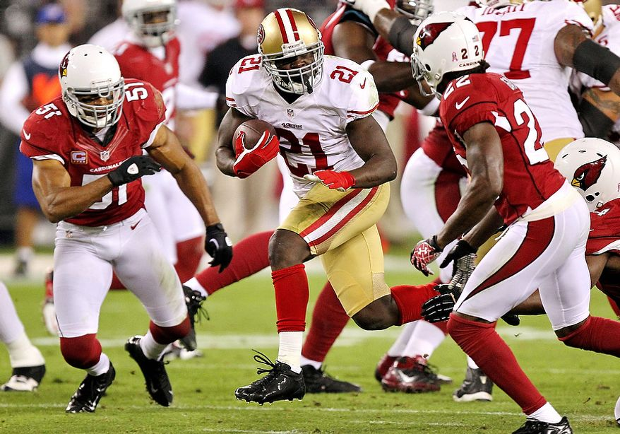 San Francisco 49ers running back Frank Gore (21) tries to gain yardage as Arizona Cardinals cornerback William Gay (22) and Paris Lenon (51) defend during the first half of an NFL football game on Monday, Oct. 29, 2012, in Glendale, Ariz. (AP Photo/Paul Connors)