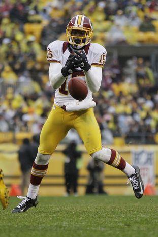 Washington Redskins wide receiver Josh Morgan (15) can't handle a pass from Washington Redskins quarterback Robert Griffin III (10) during the third quarter of an NFL football game against the Pittsburgh Steelers  in Pittsburgh, Sunday, Oct. 28, 2012. The Steelers won 27-12. (AP Photo/Gene J. Puskar)