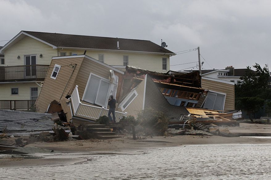 A man photographs a home damaged during a storm at Breezy Point in the New York City borough of Queens Tuesday, Oct. 30, 2012.  The fire destroyed between 80 and 100 houses Monday night in an area flooded by the superstorm that began sweeping through earlier. (AP Photo/Frank Franklin II)