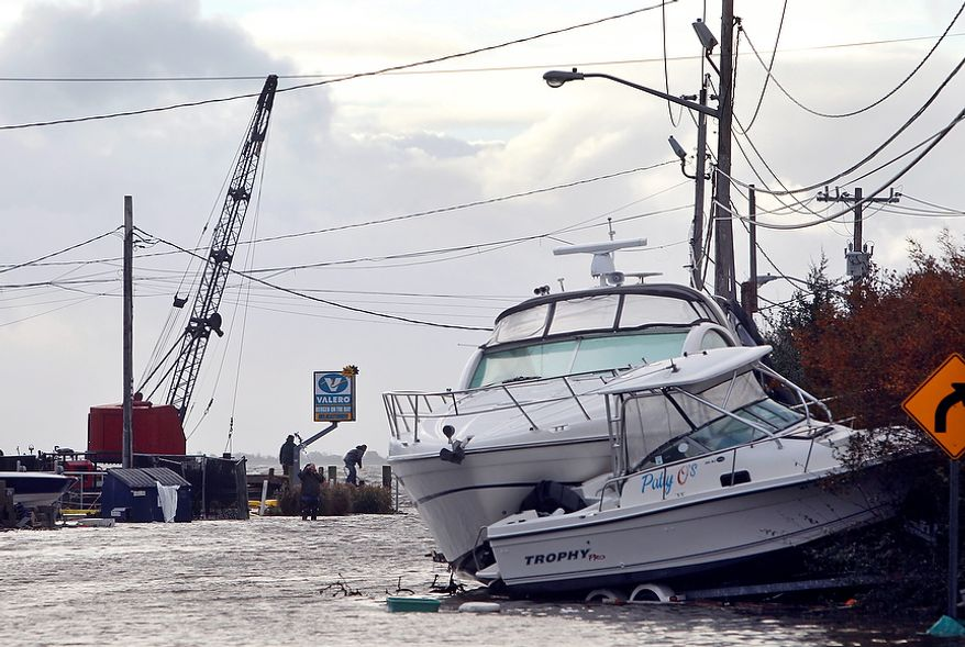 Boats lie piled up as people work to secure a fuel dock in the wake of superstorm Sandy, Tuesday, Oct. 30, 2012, in West Babylon, N.Y. The storm that made landfall in New Jersey on Monday evening with 80 mph sustained winds killed at least 16 people in seven states, cut power to more than 7.4 million homes and businesses from the Carolinas to Ohio, caused scares at two nuclear power plants and stopped the presidential campaign cold. (AP Photo/Jason DeCrow)