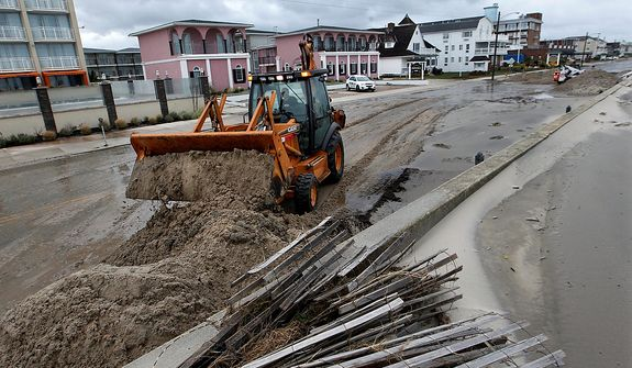 Workers use heavy machinery to clean up damage from superstorm Sandy Tuesday morning, Oct. 29, 2012, in Cape May, N.J., after a storm surge from Sandy pushed the Atlantic Ocean over the beach and across Beach Avenue.  (AP Photo/Mel Evans)