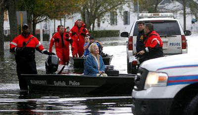 Elaine Belviso, 72, is rescued from her flooded home by Suffolk County police after being trapped there overnight by superstorm Sandy, Tuesday, Oct. 30, 2012, in Babylon, N.Y. Sandy arrived along the East Coast and morphed into a huge and problematic system, putting more than 7.5 million homes and businesses in the dark and causing a number of deaths. (AP Photo/Jason DeCrow)