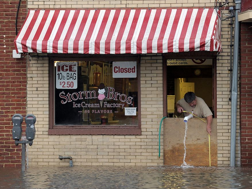 Sveinn Storm, owner of Storm Bros. Ice Cream Factory measures the flood waters outside his store in Annapolis, Md., Tuesday, Oct. 30, 2012, in the aftermath of  Superstorm Sandy that passed through the East Coast.  (AP Photo/Susan Walsh)