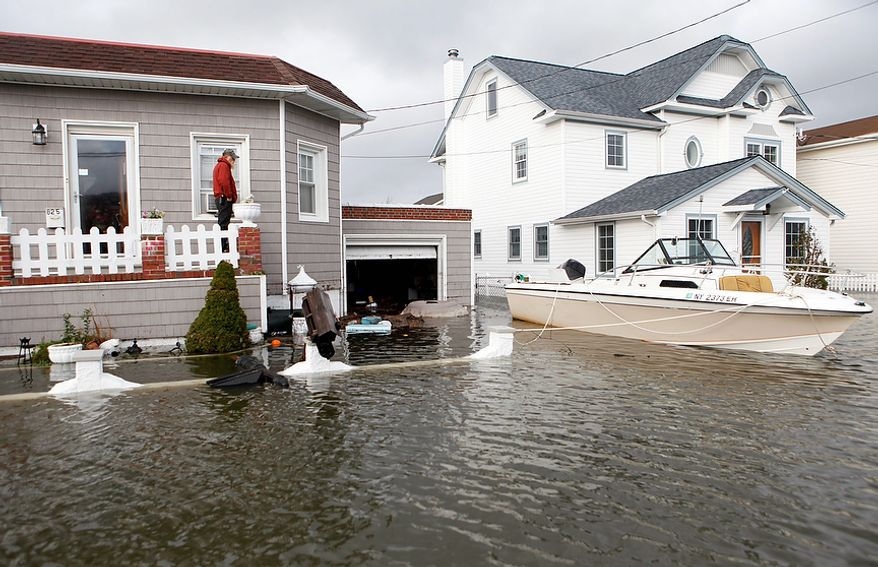 A boat floats in the driveway of a home in the aftermath of superstorm Sandy, Tuesday, Oct. 30, 2012, in Lindenhurst, N.Y. (AP Photo/Jason DeCrow)