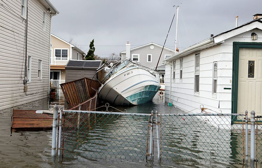 A boat lies toppled between two flooded houses in the aftermath of superstorm Sandy, Tuesday, Oct. 30, 2012, in Lindenhurst, N.Y. (AP Photo/Jason DeCrow)