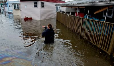 Andrea Grolon walks through waist-deep water in the Metropolitan Trailer Park in Moonachie, N.J. on Tuesday, Oct. 30, 2012. Grolon, a resident of the trailer park, was wading through oil covered water to help others get to rescue vehicles in the wake of superstorm Sandy. (AP Photo/Craig Ruttle