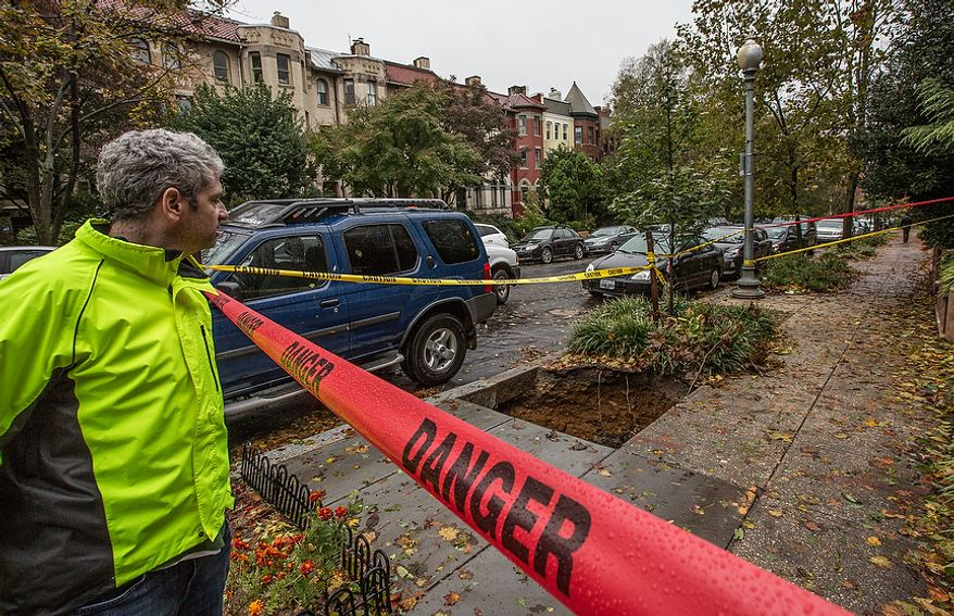 Tom Hershenson, a resident of D.C., peers over to a sink hole which is roped off on the 1900 block of Biltmore St NW., in Washington, D.C., Tuesday, October 30, 2012. Wind and heavy rain from hurricane Sandy caused the sink hole to open, making it a dangerous area for residents. (Andrew S. Geraci/The Washington Times)