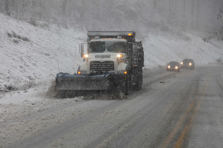 Snowplows thunder through the mountains of West Virginia as the superstorm strikes the region on Monday evening, Oct. 29, 2012. In the higher elevations of the mountains, there could be from 2 to 3 feet of snow and blizzard conditions through Tuesday. (AP Photo/Robert Ray)