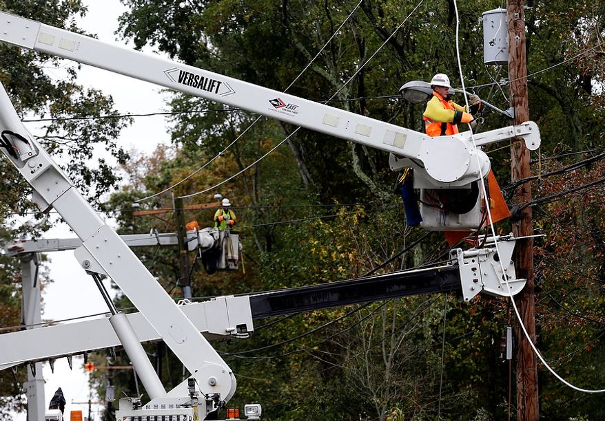 Utility crews work on damaged power lines in the aftermath of superstorm Sandy in Berlin, Md. on Tuesday, Oct. 30, 2012. (AP Photo/Alex Brandon)