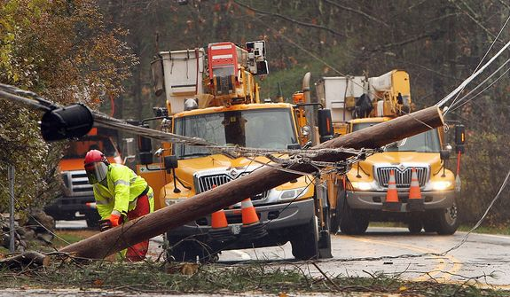 Crews work to clean up downed power lines in the aftermath of superstorm Sandy, Tuesday, Oct. 30, 2012, in Milton, N.H. Thousands of New Hampshire residents and businesses are without power. (AP Photo/Jim Cole)