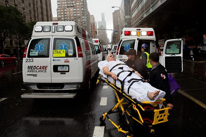 A patient is wheeled to an ambulance in the rain during an evacuation of New York University Tisch Medical, Tuesday, Oct. 30, 2012, in New York. Hurricane Sandy marched slowly inland, leaving millions without power or mass transit, with huge swatches of the nation's largest city unusually vacant and dark. New York was among the hardest hit, with its financial heart in Lower Manhattan shuttered for a second day and seawater cascading into the still-gaping construction pit at the World Trade Center. (AP Photo/ John Minchillo)