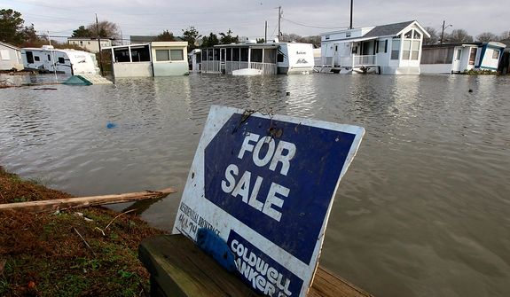 A for sale sign sits near flooded trailer homes in South Kingstown, R.I., Tuesday, Oct. 30, 2012. Beach cottages were destroyed, businesses were flooded and a quarter of the state was without power Tuesday after superstorm Sandy blew through Rhode Island. (AP Photo/Steven Senne)