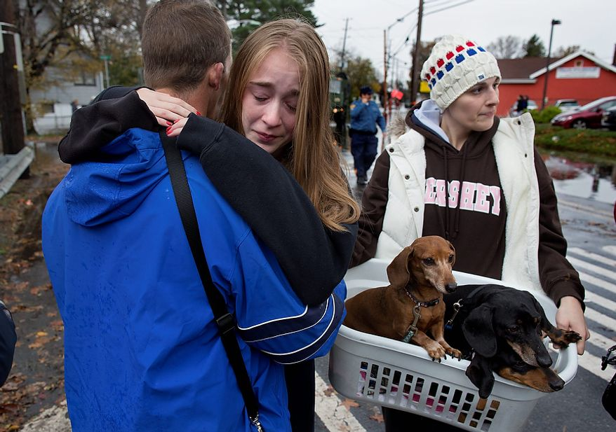 Olivia Loesner, 16, hugs her uncle, Little Ferry Deputy Fire Chief John Ruff, after she was brought from her flooded home in a boat in Little Ferry, N.J., Tuesday, Oct. 30, 2012, in the wake of superstorm Sandy. At right carrying pets, is her mother, Janice Loesner. (AP Photo/Craig Ruttle)