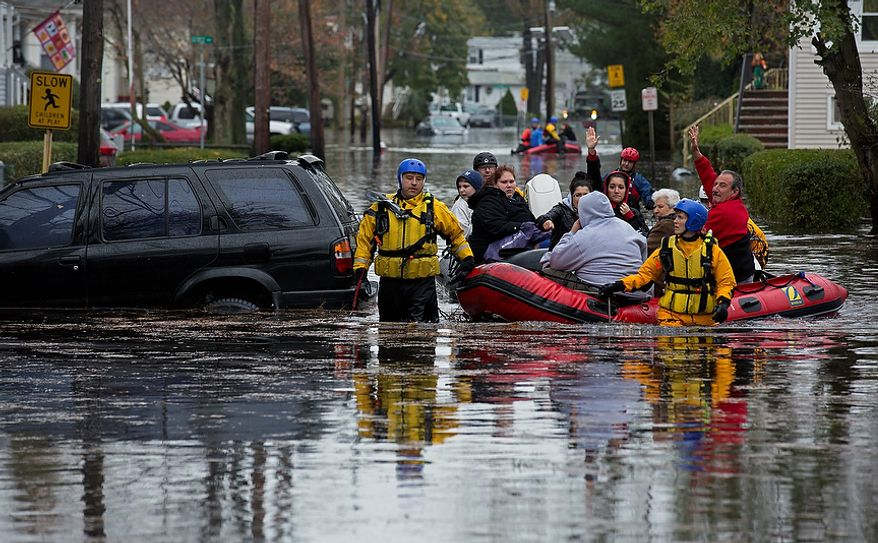 People, some waving to those on dry ground, are rescued by boat in Little Ferry, N.J. Tuesday, Oct. 30, 2012 in the wake of superstorm Sandy. Sandy, the storm that made landfall Monday, caused multiple fatalities, halted mass transit and cut power to more than 6 million homes and businesses. (AP Photo/Craig Ruttle)