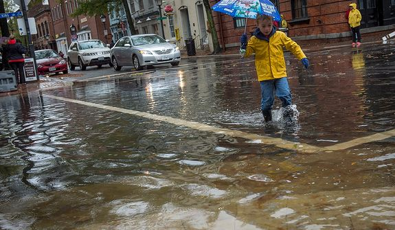James McConnon, 5, of Alexandria, Va., crosses King Street by way of flood water, as people venture out to survey the damage in Old Town Alexandria, Va., Tuesday, Oct. 30, 2012, the day after Hurricane Sandy slammed into the region. Flood water in Old Town is slightly higher than normal after a heavy rain. (Rod Lamkey Jr./The Washington Times)