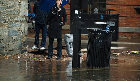 A woman stands at the corner of King and S.Union Streets as people venture out to survey the damage in Old Town Alexandria, Va., Tuesday, Oct. 30, 2012, the day after Hurricane Sandy slammed into the region. Flood water in Old Town is slightly higher than normal after a heavy rain. (Rod Lamkey Jr./The Washington Times)