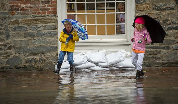 James McConnon, 5, (left) and his sister Ryan McConnon, 7, of Alexandria, Va., play in the flood waters on King Street as people venture out to survey the damage in Old Town Alexandria, Va., Tuesday, Oct. 30, 2012, the day after Hurricane Sandy slammed into the region. Flood water in Old Town is slightly higher than normal after a heavy rain. (Rod Lamkey Jr./The Washington Times)