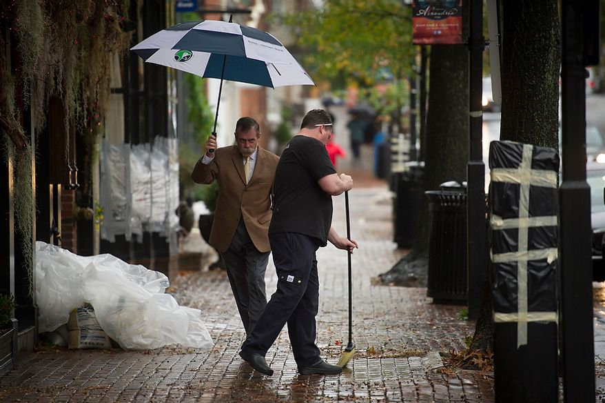 A man passes by and navigates past O'Connell's Restaurant General Manager Doug Gruenberg (right) as he sweeps small debris from the sidewalk in front of his restaurant as people venture out to survey the damage in Old Town Alexandria, Va., Tuesday, Oct. 30, 2012, the day after Hurricane Sandy slammed into the region. Flood water in Old Town is slightly higher than normal after a heavy rain. (Rod Lamkey Jr./The Washington Times)