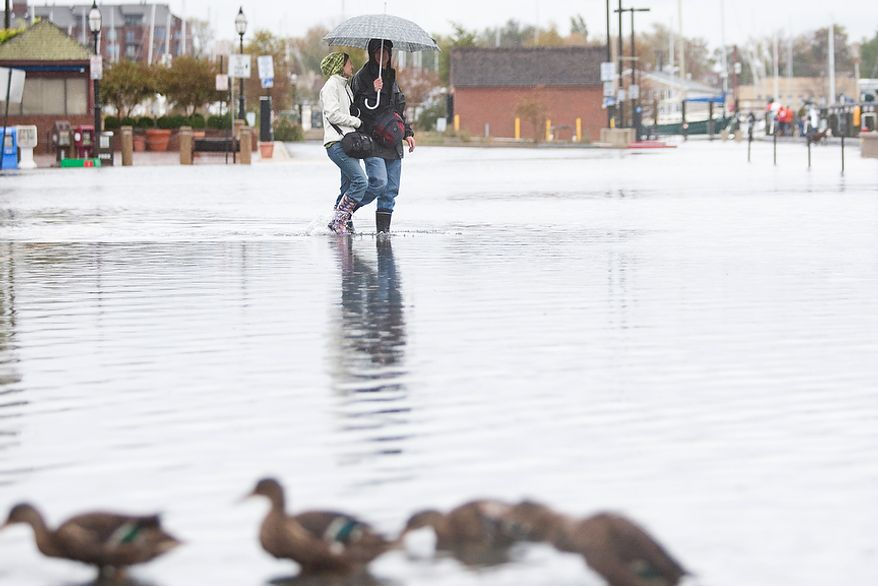 Sofie Lamartin, 22, from Annapolis, Md., left, walks with Erik Dronberger, 27, from Annapolis Md., walks though flooded Dock St., Annapolis Md., Tuesday, Oct. 30, 2012. The storm left early a foot and half of water along Dock St. but the stores are more worried about the tide which rises at 5:45pm and could bring another two feet of water. (Craig Bisacre/The Washington Times)