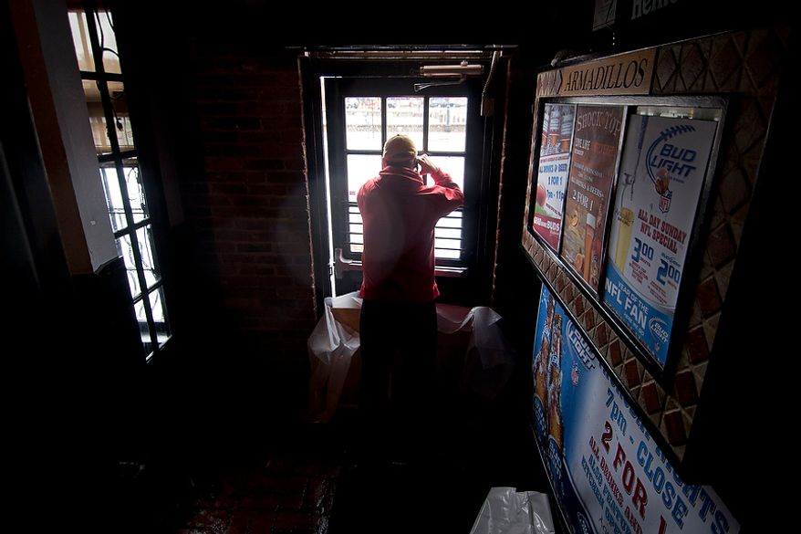 John O'Leary, 41, from Annapolis, Md., looks out of Armadillos restaurant front door at Dock St. which had nearly a foot and half of water, Annapolis, Md., Tuesday, Oct. 30, 2012. The storm left early a foot and half of water along Dock St. but the stores are more worried about the tide which rises at 5:45pm and could bring another two feet of water. (Craig Bisacre/The Washington Times)